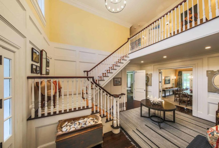 Classic foyer with dark hardwood flooring and yellow walls dominated by white wainscoting. It is completed with an oval coffee table over a gray rug along with a wooden bench on the stair landing.