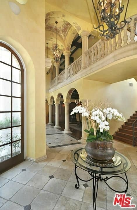Spanish style foyer with a large glazed window and a wrought iron table topped with an antique flower vase. It has limestone flooring and a hallway to the left that's framed with open archways.