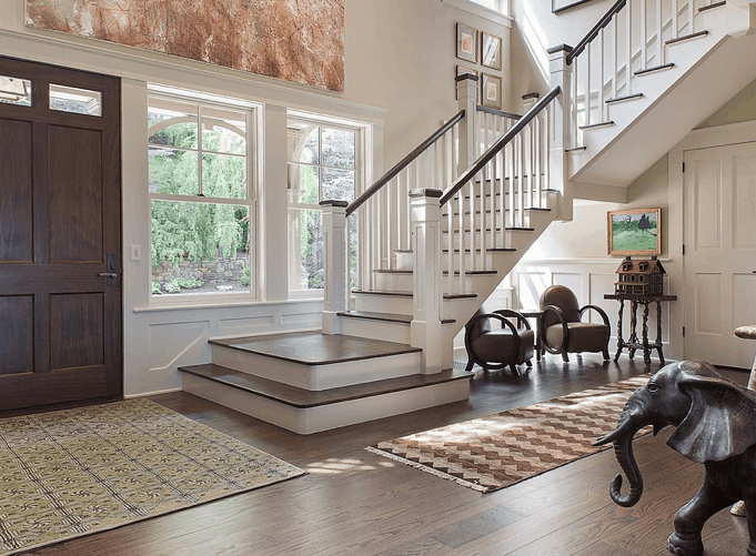 Natural light streams in through the glazed windows in this entry hall with a wooden front door and wide plank flooring topped by patterned rugs. It includes an elephant sculpture and a seating area situated underneath the staircase.
