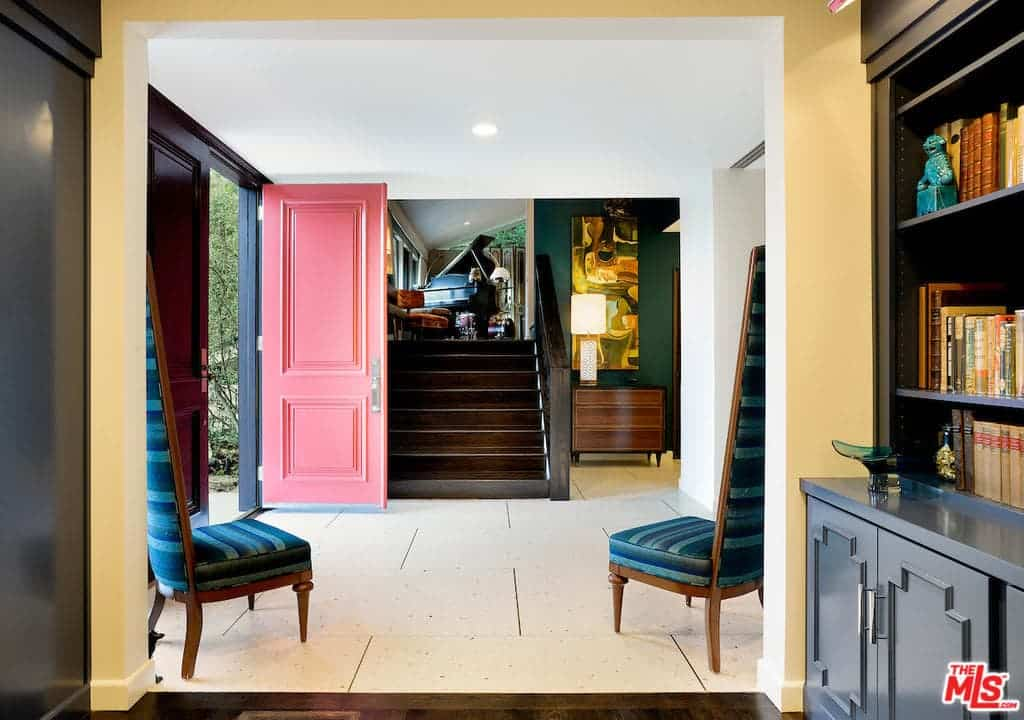 The multi-colored entry hall offers a red front door and a pair of striped high back chairs facing the dark wood staircase. It includes a wooden dresser with a warm table lamp on top accented by an abstract painting against the emerald green wall.