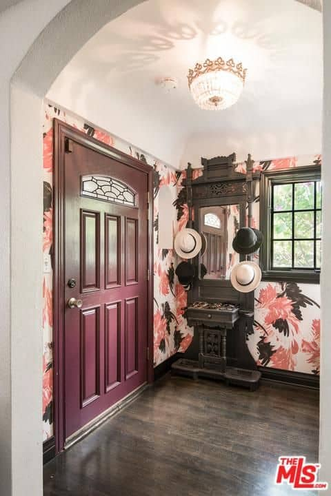 Clad in floral wallpaper, this entry hall boasts a plum door and a dark wood table with mirror and hat rack blending in with the hardwood flooring. It is completed with a lovely flush mount light and a framed window that invites natural light in.