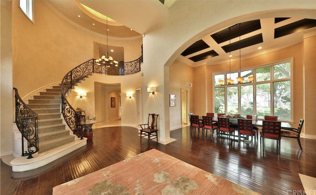 Warm foyer showcases a large floral rug and an archway that opens to the dining area. It includes a wooden chair and an ornate curved staircase lighted by a wrought iron chandelier.