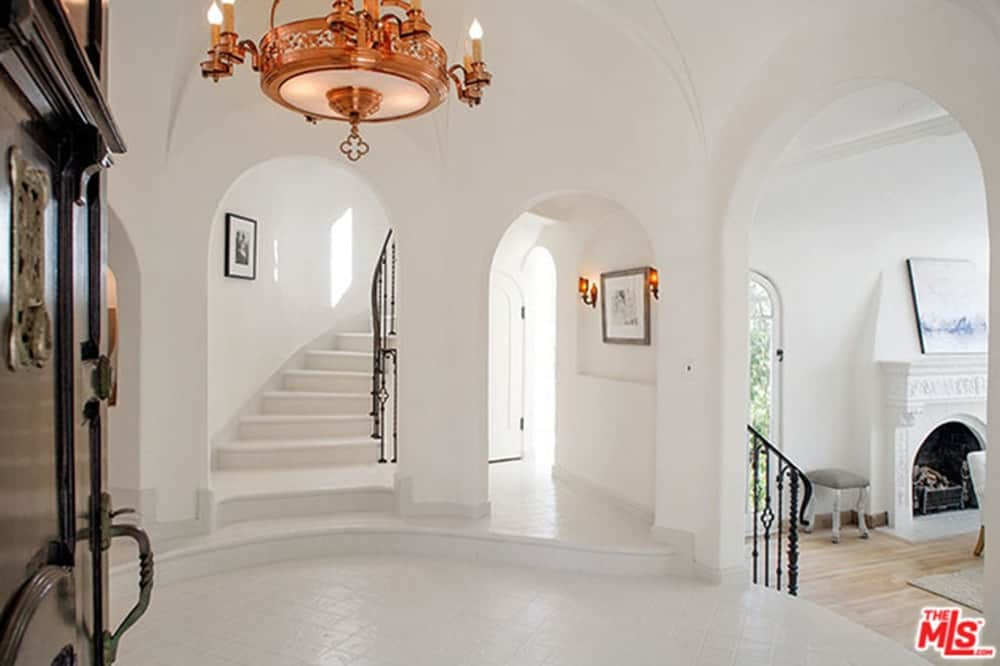 An all white foyer with open archways and tiled flooring contrasted by a black entry door and wrought iron railings. It is illuminated by a gorgeous copper chandelier that hung from the dome ceiling.