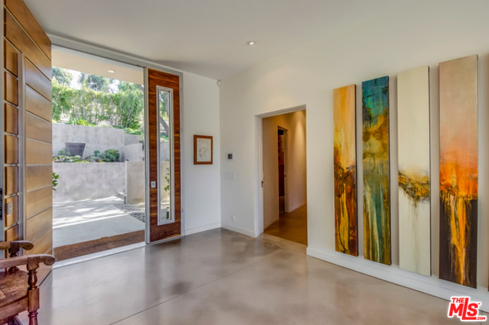 Rectangular artworks bring a pop of colors in this foyer with a wood plank door and concrete flooring complemented by a wooden armchair.
