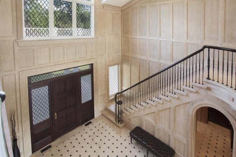A bird's eye view of this entry hall boasting a concrete staircase along with white tiled flooring and full height wainscoted walls contrasted by the dark wood front door and a black tufted bench.
