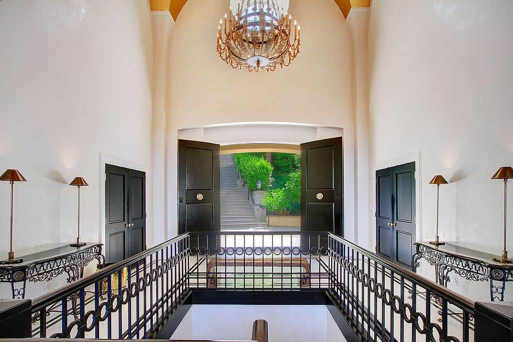 A black double door opens to this entry hall with a wooden bench and ornate console tables facing each other. It is illuminated by a classy candle chandelier that hung from the vaulted ceiling.