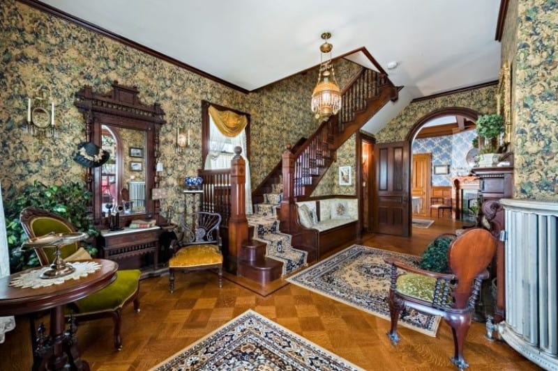 Victorian foyer with a classic wallpaper and rich hardwood flooring topped by patterned rugs. It is completed with cushioned seats and dark wood vanity matching with the round table.