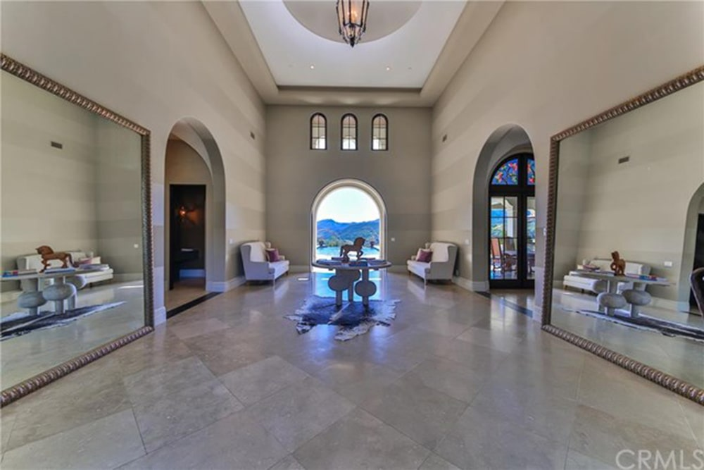 Facing wingback seats along with open archways and large mirrors create perfect symmetry in this entry hall with a warm pendant light and a stylish round table that sits on a cowhide rug over limestone flooring.