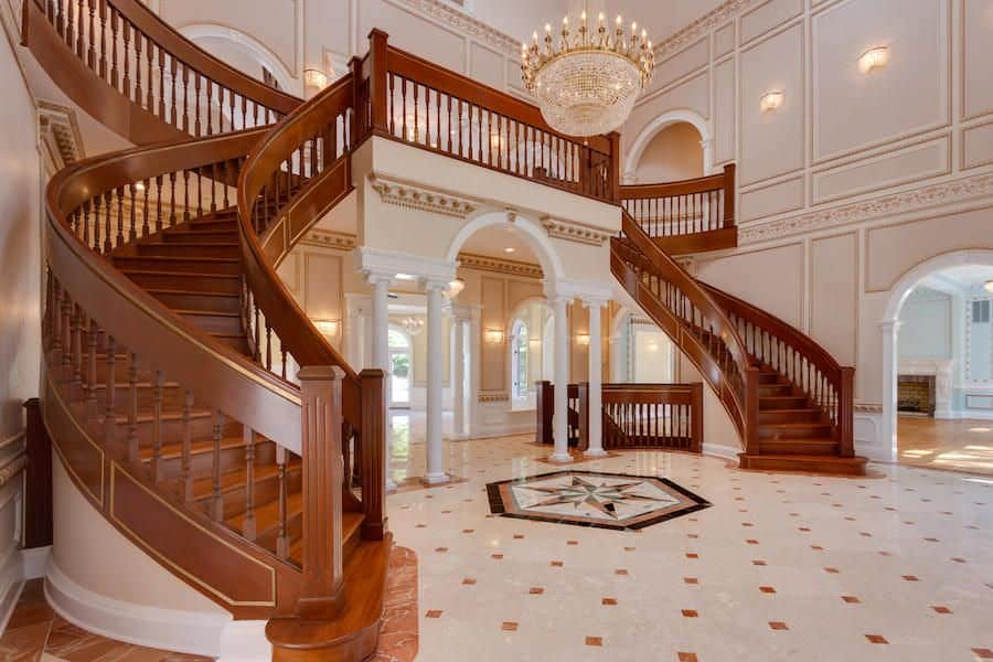 A grand foyer with a glamorous staircase with hardwood steps and wooden rails. The home boasts gorgeous tiles flooring and elegantly decorated walls, along with a two-storey ceiling lighted by a glamorous chandelier.