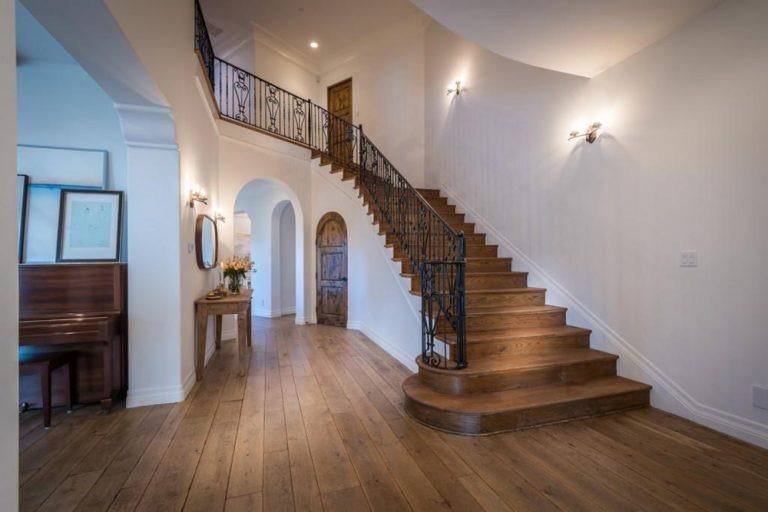 A spacious foyer featuring hardwood flooring and white walls lighted by classy wall lights. This foyer offers a gorgeous staircase with wooden steps.