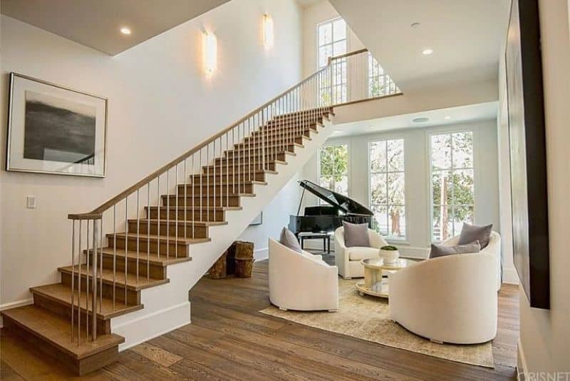 This home features hardwood floors topped by an area rug where the living space furniture are set. There's a staircase with hardwood steps leading to the home's second floor.