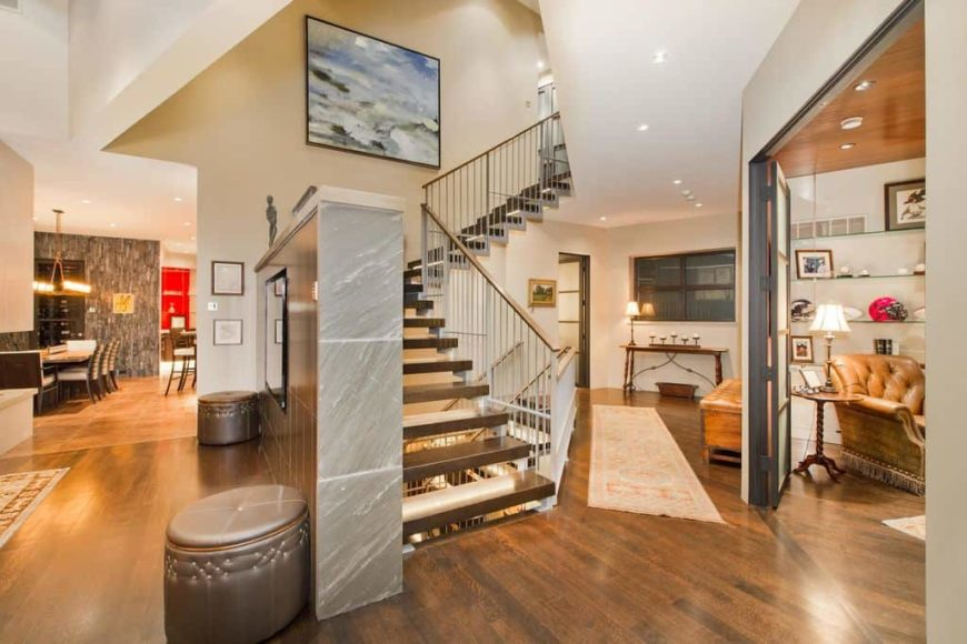 This home features hardwood flooring and white walls. It offers a beautiful staircase with hardwood steps. The entry leads to the living space on the side and to the kitchen and dining on the other side.