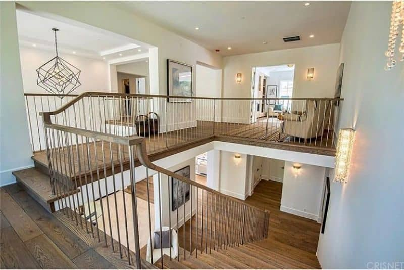 A large home with a staircase featuring hardwood steps matching the flooring. The home is lighted by gorgeous wall lights and recessed ceiling lights.