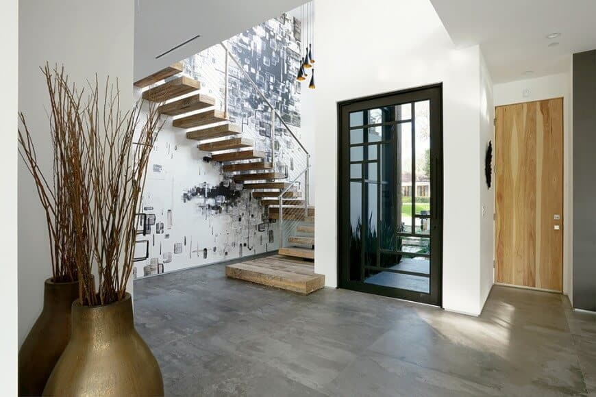 A spacious entry with gray flooring and white walls. The staircase on the side features hardwood steps and a glass railing, along with a stylish wall on the side.