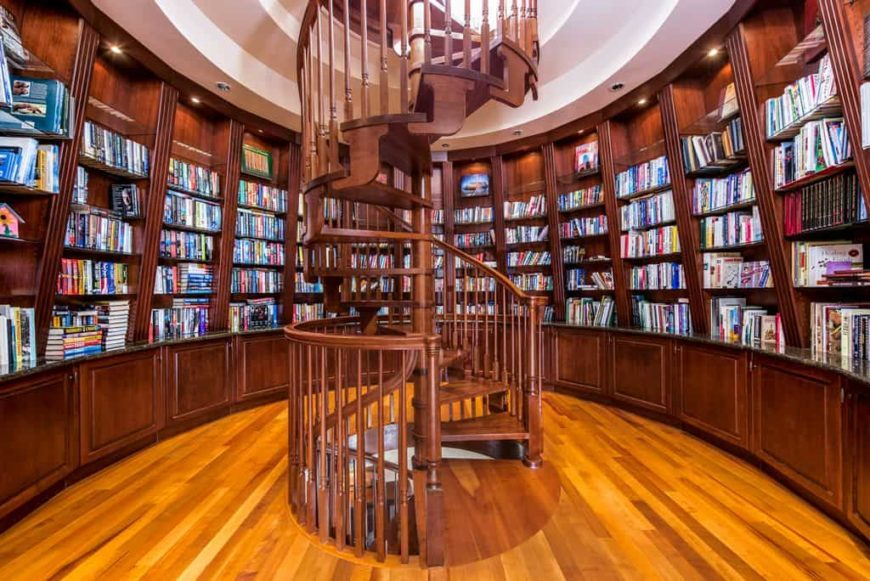 This home boasts a stunning wooden spiral staircase leading to the home's gorgeous library with wooden bookshelves.