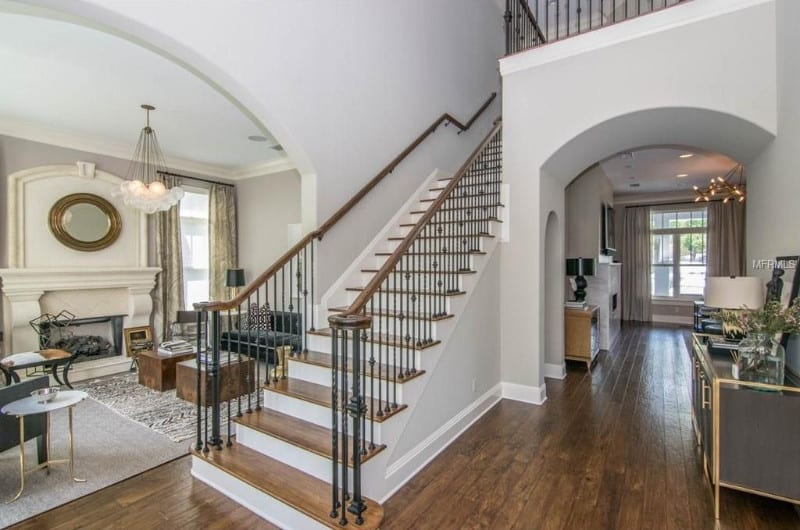 A gorgeous foyer with hardwood floors and a two-storey ceiling. There's a staircase leading to the second floor with hardwood steps. The home's living room is on the side of the area.
