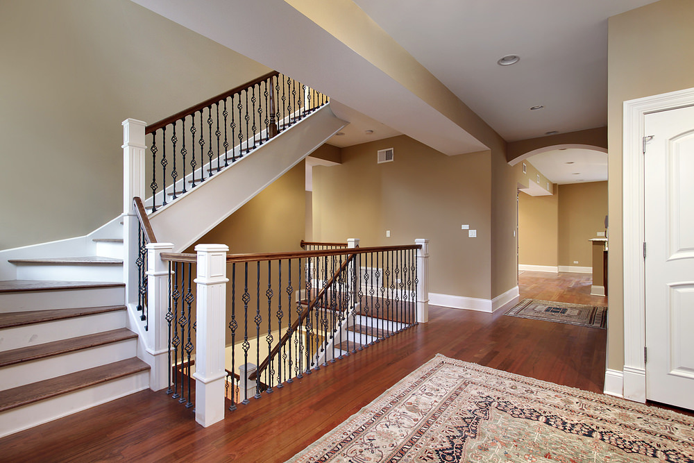 This home's hall features hardwood flooring topped by a stylish area rug. The staircase features hardwood steps and iron railings.