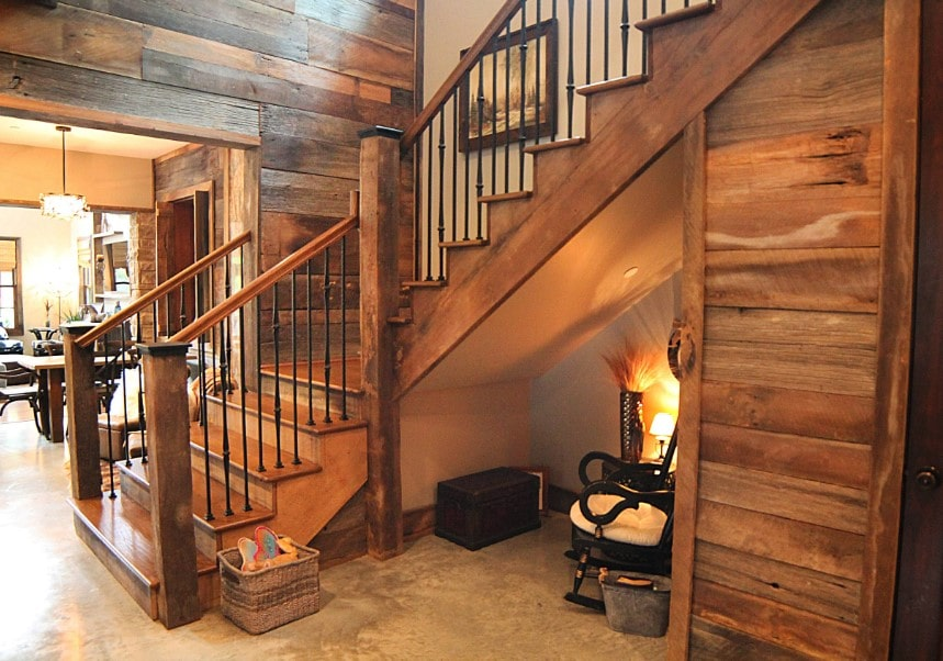 A foyer featuring a staircase with hardwood steps and hardwood handrails, along with iron railings. The home also has a stylish rustic wall.