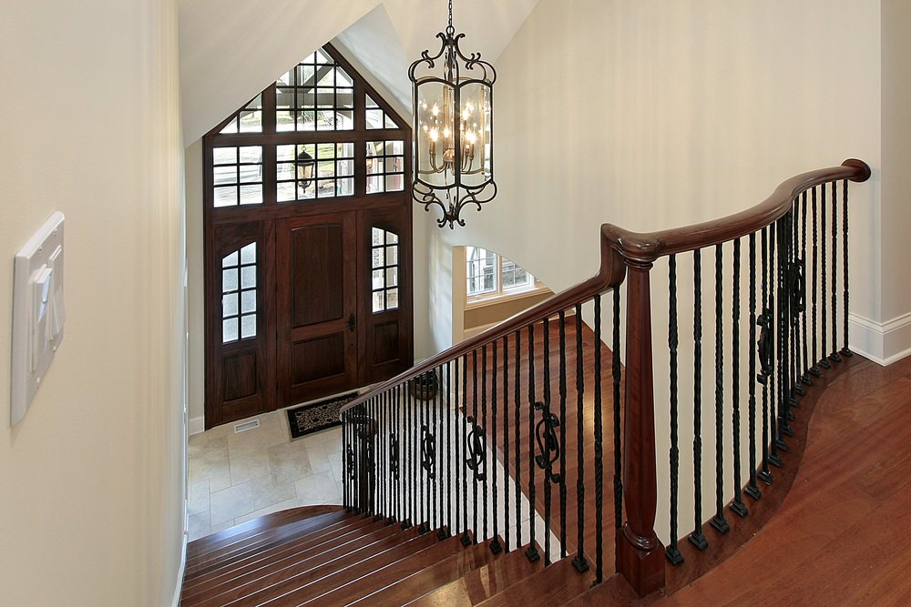 A foyer boasting a classy staircase with hardwood steps and iron railings. The area is lighted by a gorgeous ceiling light hanging from the high ceiling.