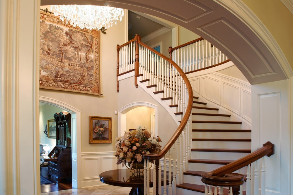 A look at this home's gorgeous staircase lighted by a grand glamorous chandelier and has an elegant wall decor on the top area of the wall.