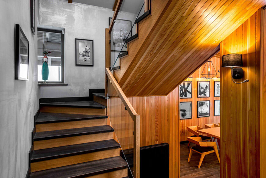 A modish looking staircase with dark hardwood steps. The gray walls of the home has framed wall arts on it.