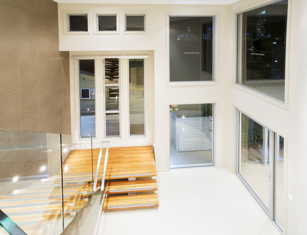 A white entry with a jaw-dropping two-storey ceiling with glass windows, along with a modish staircase with glass railings and hardwood steps.