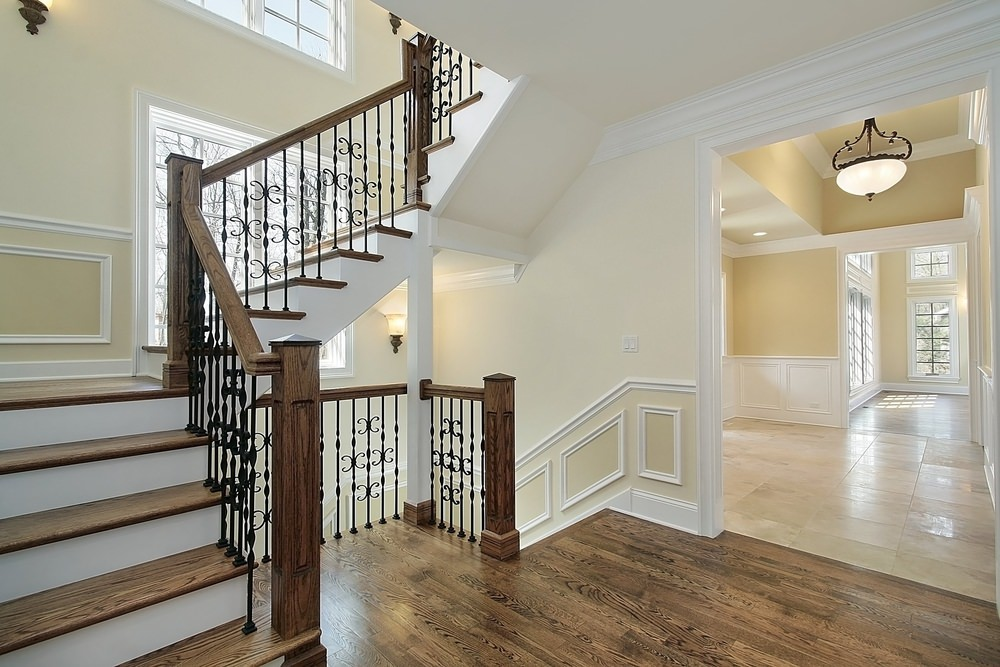 An empty home's foyer featuring hardwood steps matching the handrails. The home boasts light yellow walls with wall lights.