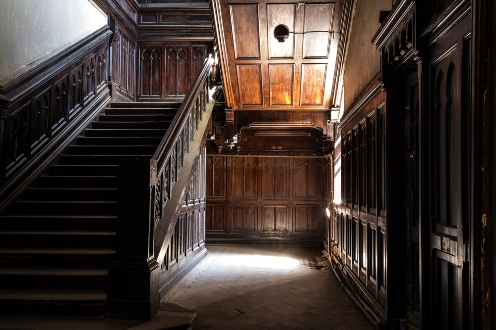 A magnificent-looking foyer with dark hardwood staircase, walls and ceiling.