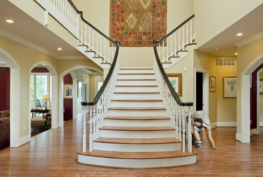 An elegant foyer with a gorgeous staircase with hardwood steps matching the hardwood flooring. The area features a two-storey ceiling.