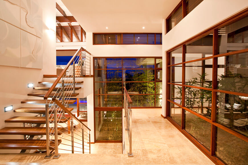 A glamorous home with elegant staircase featuring hardwood steps matching the handrails. The home boasts glass windows.