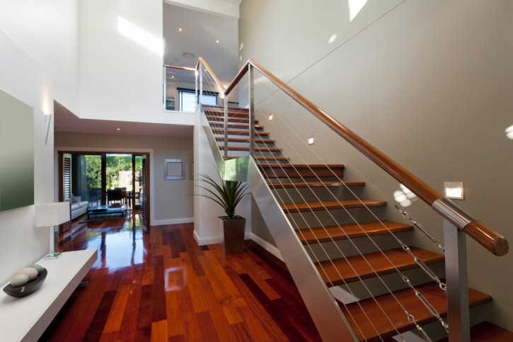 Modern home with stylish hardwood floors and a high ceiling. It also offers a modish staircase with well-polished hardwood steps and white walls.