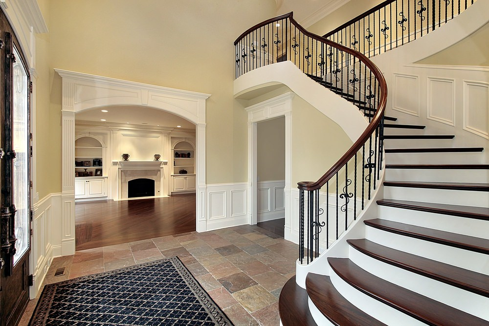 This home's foyer features tiles floors and yellow walls, together with a gorgeous staircase with classy railings and hardwood steps.