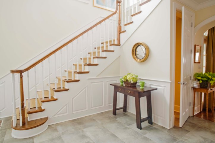 A focused look at this entry's staircase with white railings and hardwood steps matching the stair's handrails. The home features gray tiles floors and white walls.