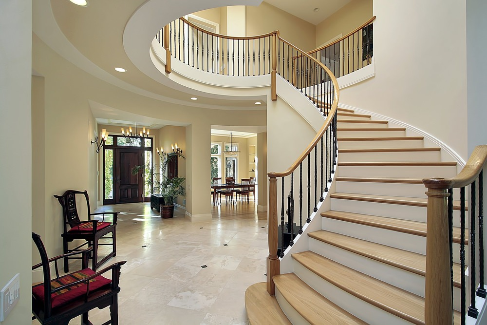 A look at this foyer's curved staircase with charming hardwood steps and handrails. The home's walls are painted with beige, along with tiles flooring.