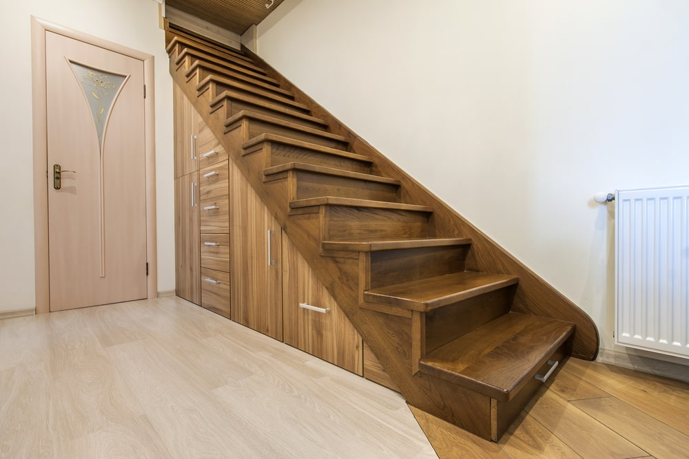 A simplistic entry with white walls and hardwood floors. The area also features a staircase with hardwood steps.