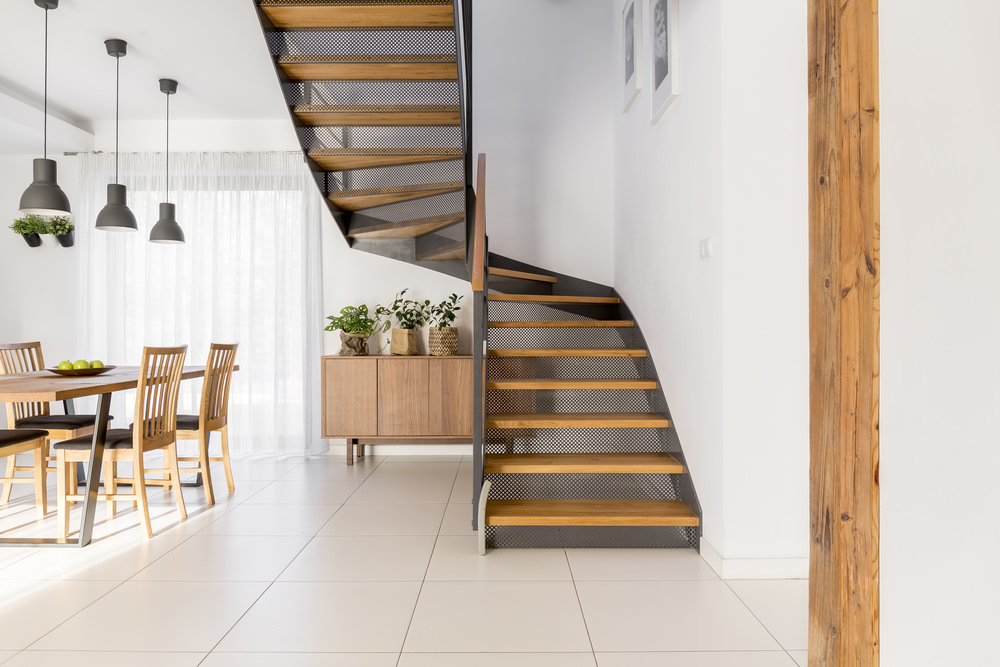 A stylish staircase with hardwood steps, set on the side of the dining table set lighted by pendant lights.