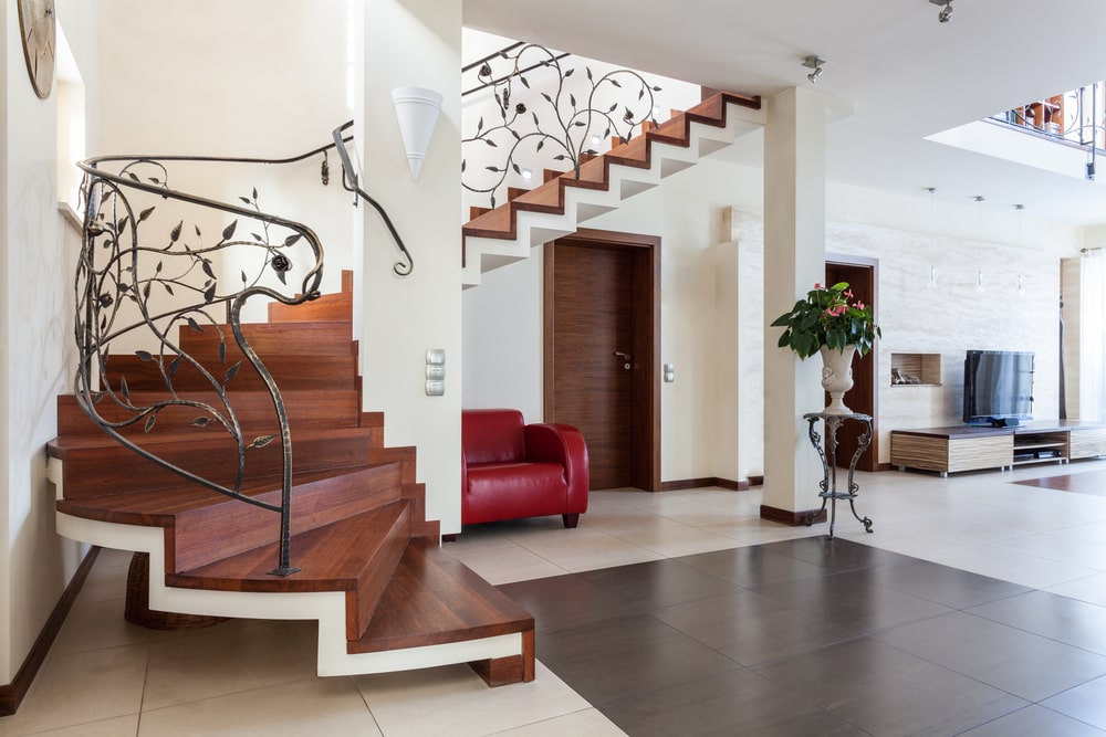 A spacious foyer boasting an elegant staircase with elegant iron railings and hardwood steps lighted by a glamorous chandelier hanging from the two-storey ceiling.
