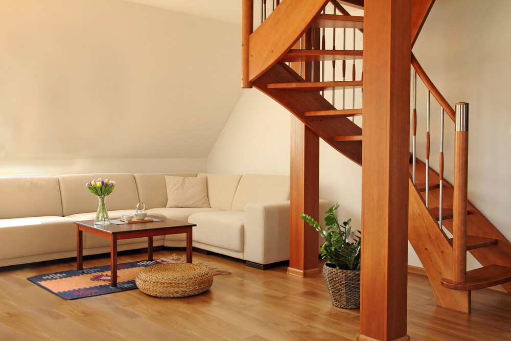 A spacious living space offering a cozy sofa set with a wooden center table on top of a small area rug. The area has a stylish wooden staircase as well.