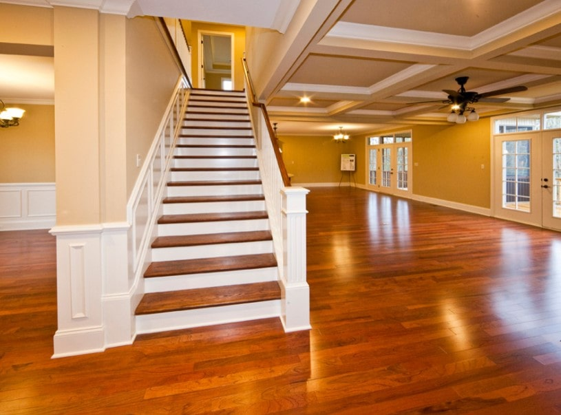 An empty home featuring hardwood floors and mustard yellow walls. The home has a straight staircase featuring hardwood steps and handrail.