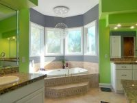 Large master bathroom with green walls, a drop-in tub by the windows, and dual sink.