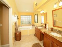 Contemporary yellow master bathroom with alcove tub and dual sink.