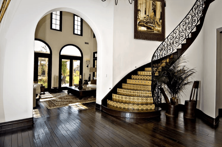 Tuscan style foyer showcases an open archway leading to the living room along with a curved staircase that's fitted with decorative tile risers and ornate railing. It is accented with a tasseled tapestry that's fixed against the white wall.