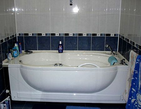 White and blue tile to finish the bathroom with molded acrylic bathtub