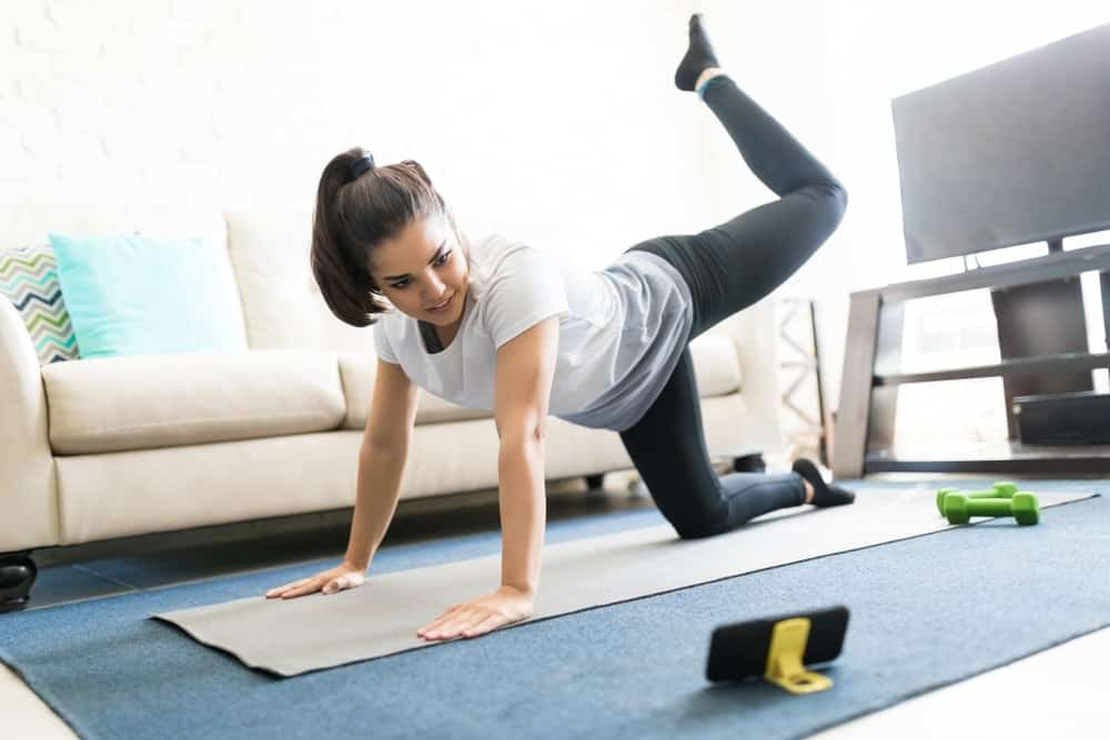 A woman doing floor exercises in her living room.