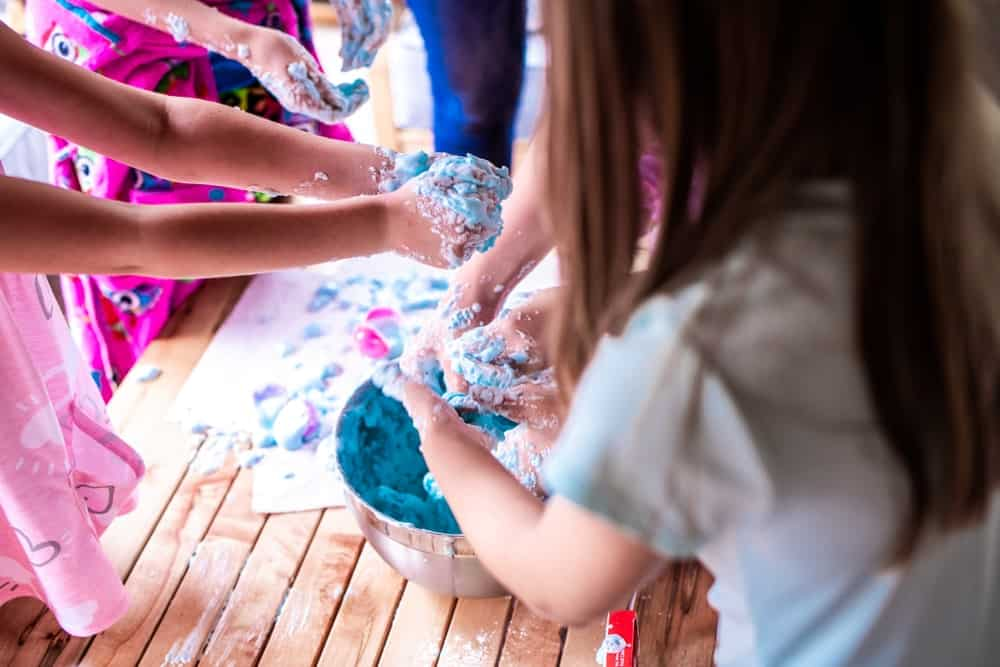 A group of girls playing with colorful frosting.