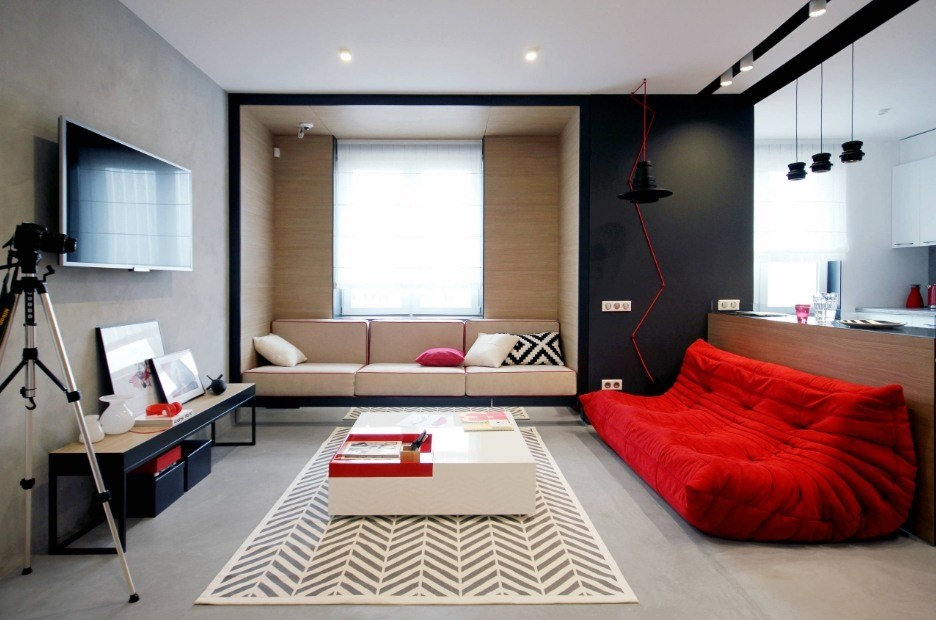 Black accent wall, wleeper at the window and red anatomic sofa in the modern boxed living