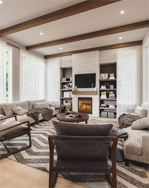 The living room with a beam ceiling, windows, a fireplace flanked by built-in shelves, and a patterned area rug on wood. Source: TheHouseDesigners.com