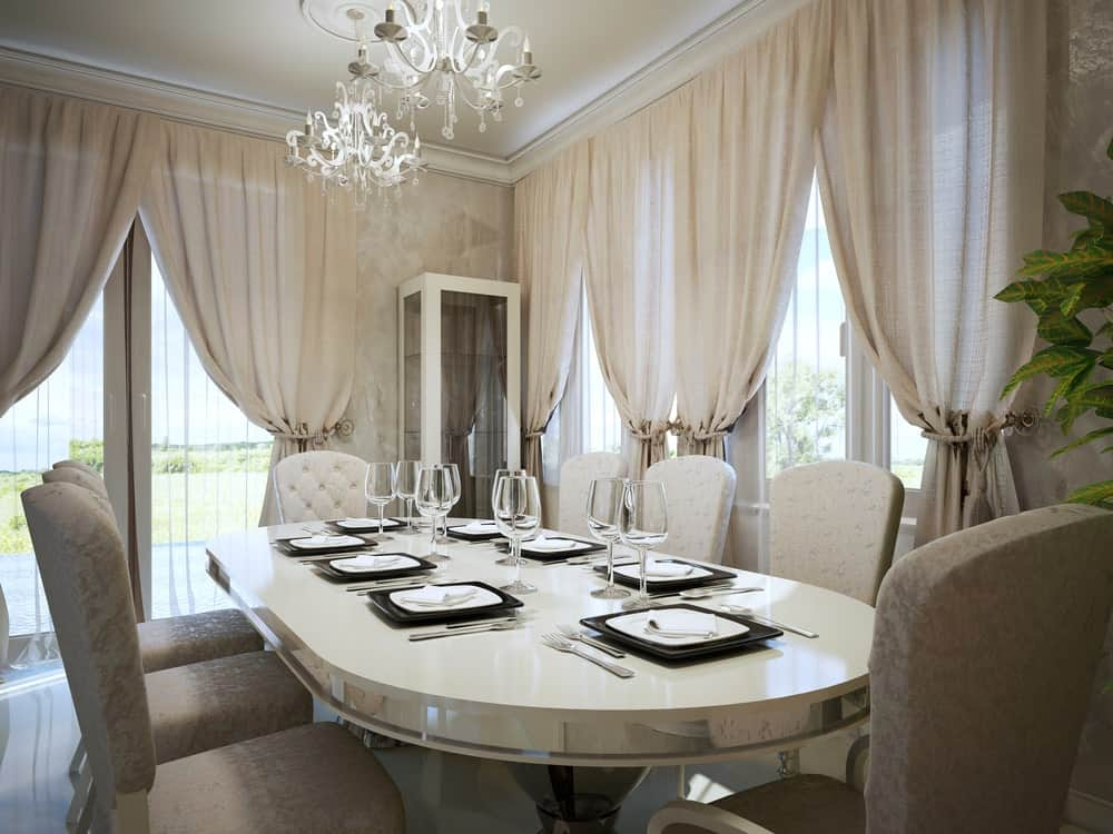 Beige dining room with French door and glazed windows covered in sheer curtains, oval dining table paired with cushioned seats, display cabinet and a pair of chandeliers.