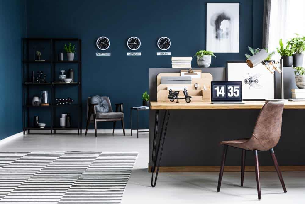 Blue home office with wall clocks, black shelving, lovely artwork, wooden desk paired with brown modern chair and a black striped rug over light flooring.