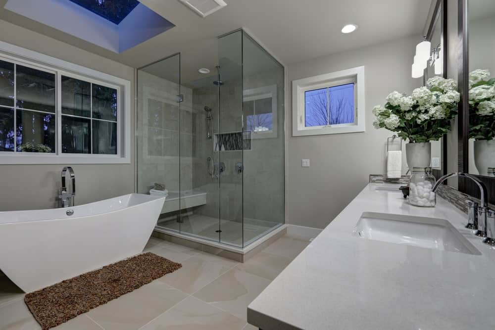 Gray master bathroom with walk-in shower, dual sink vanity, white framed windows, brown rug over beige tiled flooring and a freestanding tub underneath a skylight.